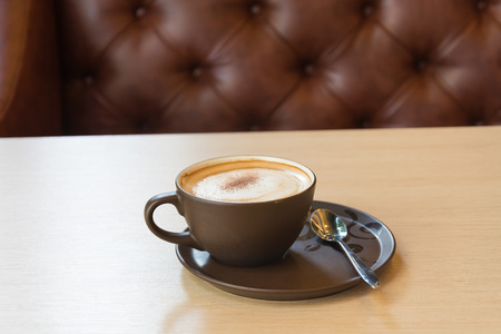 capuchino: a cup of coffee on wood table