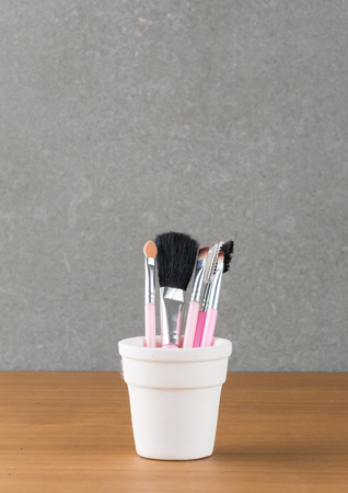 cosmetic brushes container on wood table photo