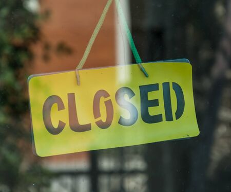 store sign: The closed sign on a glass door