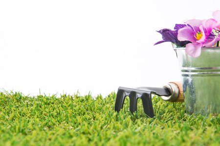 turf flowers: green grass turf on white with flowerpot and fork Stock Photo