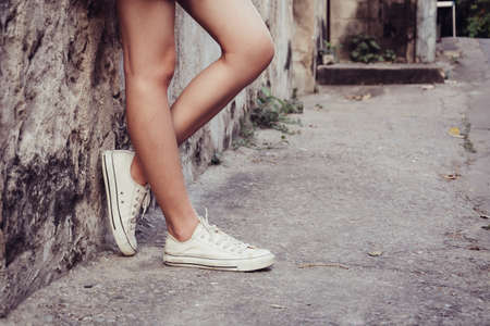 hugging legs: leg girl with white shoes : film texture in vintage style