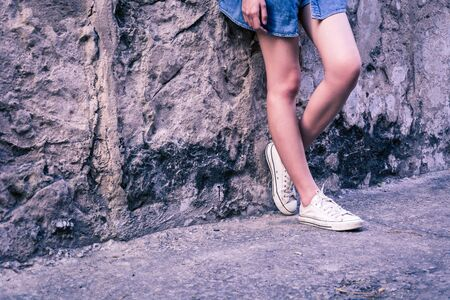hugging knees: leg girl with white shoes : film texture in vintage style