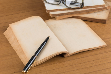 write a letter: old book with pen on wood table