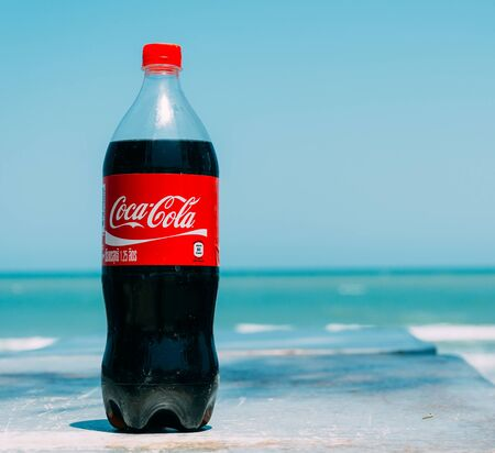 carbonated: Pranburi,Thailand. March 31,2015.Coca cola bottle with sea background. Coca-Cola is a carbonated soft drink sold in stores, restaurants