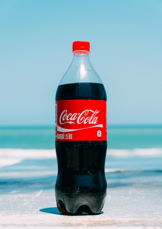 cola bottle: Pranburi,Thailand. March 31,2015.Coca cola bottle with sea background. Coca-Cola is a carbonated soft drink sold in stores, restaurants