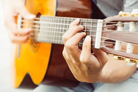 fretboard: hand playing on acoustic guitar - soft focus with vintage filter