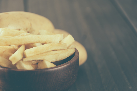a portion: french fries on wood background - soft focus with vintage film filter