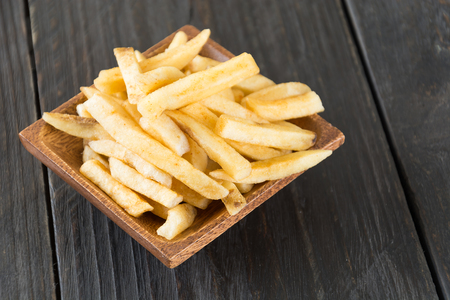 a portion: french fries on wood background