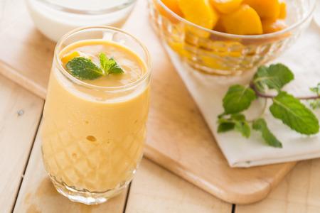 mango: świeże mango smoothie na tle drewna