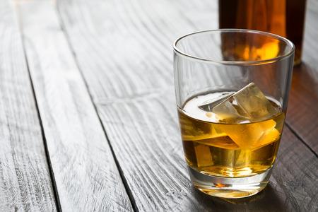 botella de whisky: wisky vaso sobre la mesa de madera Foto de archivo