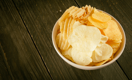 nosh: potato chips on wood - soft focus with vintage film filter Stock Photo