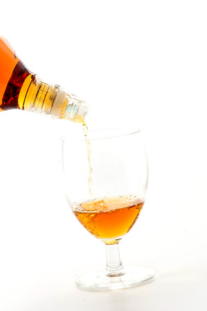 alcoholic drink: pouring wisky on white background Stock Photo