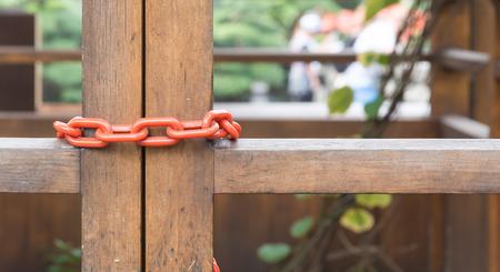 keep gate closed: chain locked on wood door Stock Photo