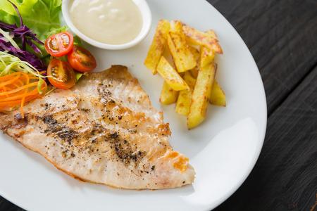 prepared food: fish steak on wood table Stock Photo