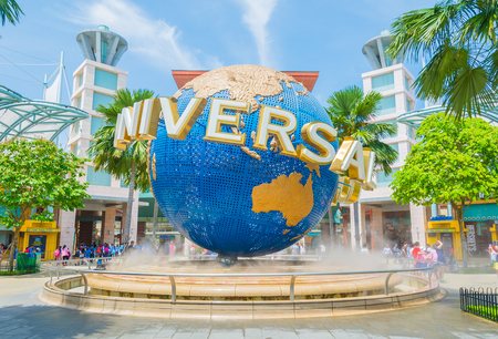 SINGAPORE - JULY 20: Tourists and theme park visitors taking pictures of the large rotating globe fountain in front of Universal Studios.