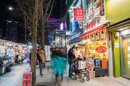 entertainment district: SEOUL, SOUTH KOREA - March 6 2016: People wander in the walking street of the Dongdaemun shopping and entertainment district at night.