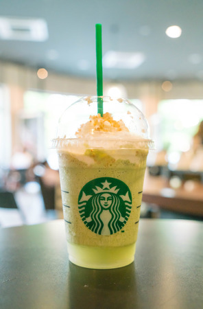 BANGKOK THAILAND- 2016 APRIL 28: Glass of Starbuck Green tea smoothie served at wood table in starbuck shop at Department store.