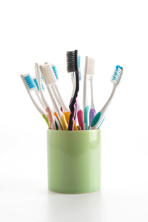 paradontosis: Multicolored toothbrushes in a water glass