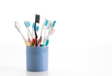 Multicolored toothbrushes in a water glass