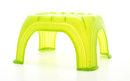 Small green plastic stool on white background
