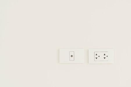 electric socket: White electric socket on the wall.
