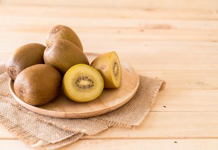 fresh golden kiwi in wood plate