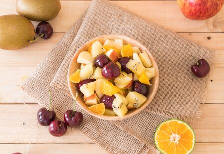 sliced fruit: mixed sliced fruit in wood bowl