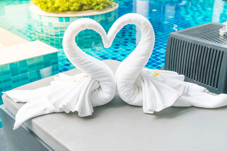 close up view of two nice towels swans on bed pool - with sunflare effect Stock Photo