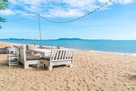 white chairs and table on beach with a view of blue ocean and clear sky Stock Photo