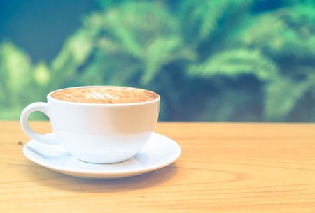 macchiato: hot caramel macchiato in coffee shop - vintage effect filter Stock Photo