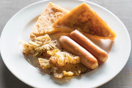 breakfast with fried pineapples, sausages and toasts on white plate
