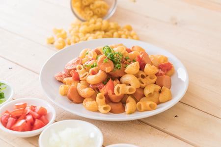 comfort food: macaroni with sausage on wood table Stock Photo