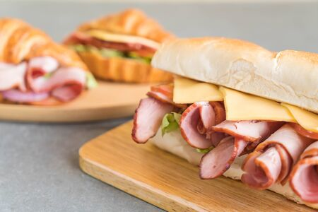 Ham and salad submarine sandwich on table background