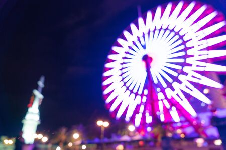 abstract blur bokeh night harbor lights background with ferris wheel Stock Photo