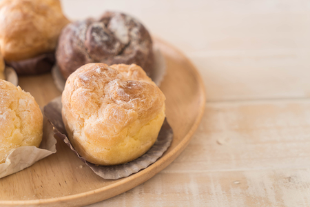creampuff: cream puff on wood plate
