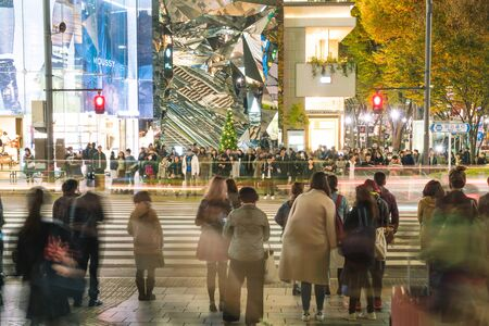 dozens: HARAJUKU, TOKYO, JAPAN - NOV 18 2015: Busy Harajuku main zebra crossing with Tokyu Plaza shopping mall in the background - dozens of shoppers and pedestrians crossing the street.