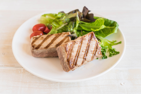 rocket lettuce: tuna steak with salad on wood table