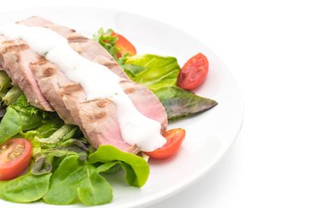 rocket lettuce: tuna steak with salad on white background