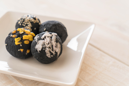 Charcoal potato ball on white plate