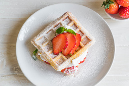 waffle with strawberry on wood table