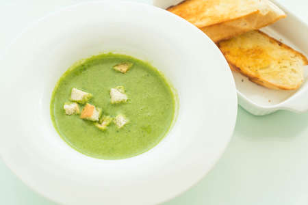 spinach soup with garlic bread on table Stock Photo