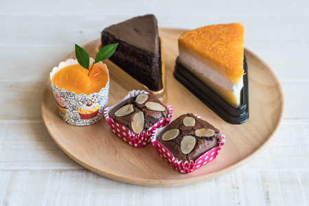 brownies, orange cup cake, golden threads cake and chocolate cake on wood
