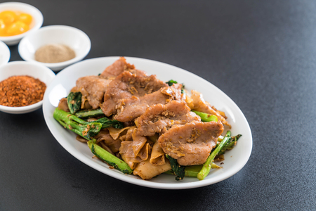 fried noodles with soy sauce and pork with condiments