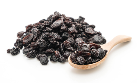 black raisins on white background Фото со стока