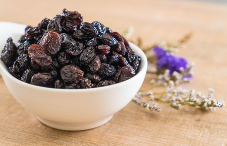 black raisins in bowl on table
