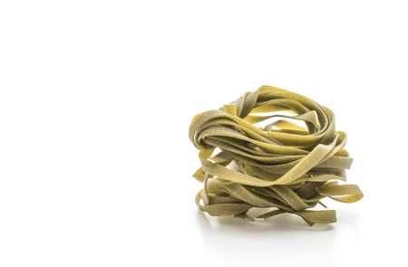 dried spinach fettuccine pasta on white background