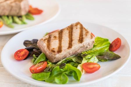 tuna steak with salad on wood table
