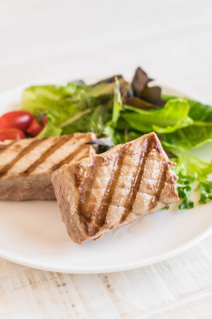 tuna steak with salad on wood table
