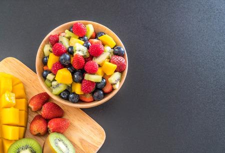 mixed fresh fruits (strawberry, raspberry, blueberry, kiwi, mango) on wood bowl Stock Photo