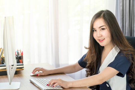 internet search: happy asian woman in office - business concept Stock Photo